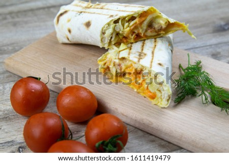 Pieces of cutted thin Armenian pita bread or lavash wrapped tomatoes, cottage cheese or curd, chicken meat, tomatoes and herbs - dill, onion, parsley with vintage knife on cutting board.