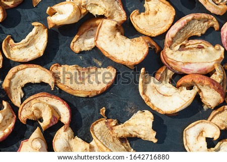 pieces of dried apples, dried fruits, dried on a black cloth in the sun