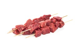 Pieces of fresh meat on bamboo skewers on a white background. Fresh meat skewers on skewers.