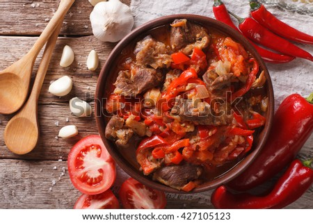 pieces of lamb cooked with onion, tomato and pepper close-up in a bowl on the table. horizontal view from above