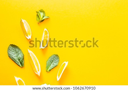 Pieces of lemon, lime and green mint leaves on a yellow background. Summer products for making lemonade. Top view, flat lay, copyspace #1062670910