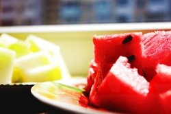 pieces of melon and watermelon cut into cubes on a plate. summer juicy still life