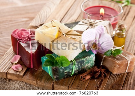 Pieces of natural soap with herbs and candle.