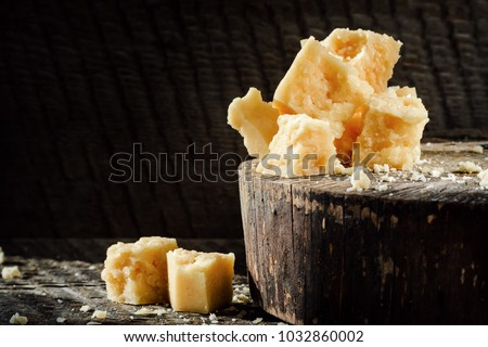pieces of Parmesan cheese on a dark wooden background. Photo with copy space