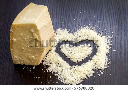 Pieces of parmesan cheese on black wood board. Parmesan is hard cheese. Top down of single tasty fresh yellow big segment piece and finely grated cheese.