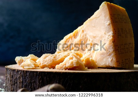 Pieces of Parmesan cheese on rustic wooden dark background, with parmesan cheese knife. Copy space