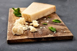 Pieces of parmigiano reggiano or parmesan cheese on wood board on stone background. Parmesan is hard cheese uses in pasta dishes, soups, risottos and grated over salads.