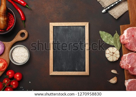 Pieces of raw pork steak on cutting board with cherry tomatoes, rosemary, garlic, red pepper, bay leaf, onion, mortar and chalk board on rusty brown background. Top view with space for your text.