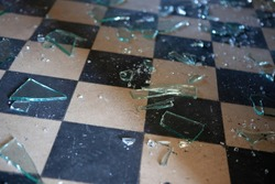 Pieces of shattered glass or mirror in an abandoned house on the floor. Shallow depth of field