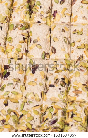 Pieces of sunflower seeds halva with pistachios displayed for sale at an weekend street food market, in soft focus, sun lightsun rays. Street food market shop counter top display turkish traditional