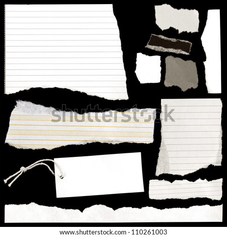 Pieces of torn paper and luggage tag on black.