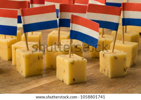 Pieces of traditional Dutch cumin cheese with a red, white and blue flag as a snack