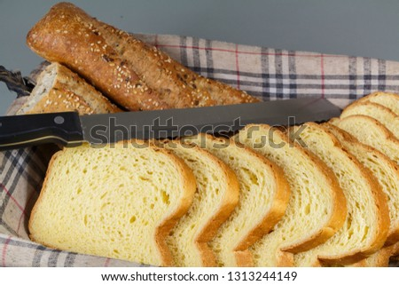 Pieces of traditional french baguette bread, slices of brioche and knife in a breadbasket