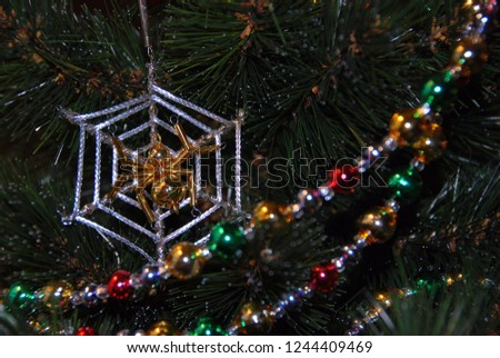 Pied bright shiny glass garland on the Christmas tree. Ornaments for a Christmas tree. Christmas decorations. Funny spider web decoration.