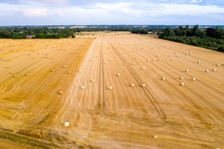 Piencourt, Normandy, France. Aerial view of straw fields with bales in rural France at sunset