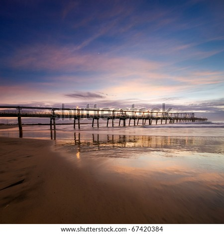 pier at dawn with interesting reflections and smooth clouds formation at square format