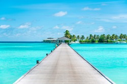 Pier at Maldives. Blue water, boats. Summer holidays photo.