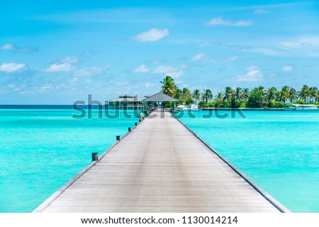 Pier at Maldives. Blue water, boats. Summer holidays photo.  #1130014214