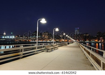 Pier at night with benches and lamps in the city.