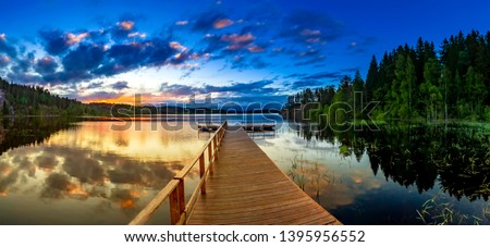 Pier at sunset in Karelia. Evening river pearce panorama. The view of the sunset from the pier. A wooden pierce leads into the water. Pier for swimming. Swimming season. Summer holidays in Karelia.