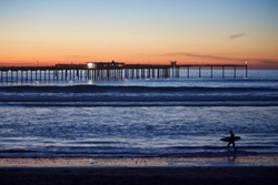 Pier at sunset with surfer walking the shore.  Waves slowly lapping against the beach cause a dramatic scene of dark moody colors.  Sunset provides a striking backdrop for the walk home.