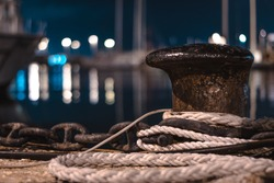 pier bollard sea ship night with lights in the background