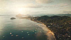 Pier cityscape aerial view at sun light. Boats, vessels, ships at shallow ocean bay water. Tropic urban scenery with buildings, lodges, cottages. Cinematic Asia nature scape with tropical mount forest