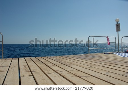 pier deck with blue sky and sea on background
