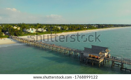 Pier in Naples by Aerial Drone. Drone flies around a fishing pier in Naples, Florida USA. Coast and the beach near the pier leaving into the ocean. Naples Beach Pier.