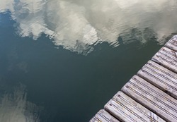 Pier in the river with reflections in the water, top view. Clouds are reflected in the water. Background with copy space. Two textures for the design. Pier made of old wooden planks.