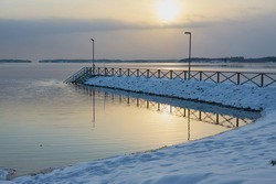 Pier in the snow at sunset on the shore of the freezing sea.