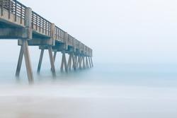 Pier on a beach during a foggy morning.