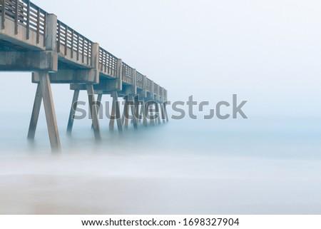 Pier on a beach during a foggy morning.  Сток-фото ©
