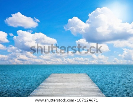 Pier on sunny day with white clouds and sun