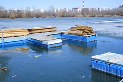 Pier on the lake. Stacked wooden planks on the dock. The lake is covered with ice. Wooden beams and boards on the street . Construction concept.