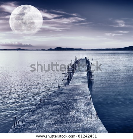 Pier on the sea at night time. Moon in the sky