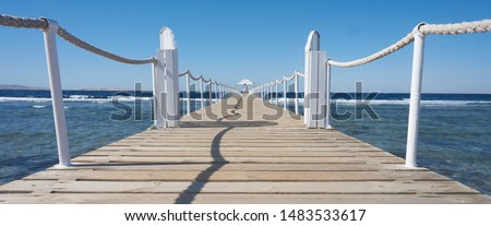 Pier on the seashore, with a girl walking along the pier into the distance. Travel.
