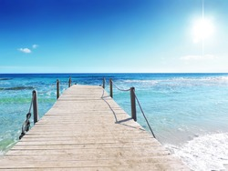 Pier or wooden bridge on a tropical beach with clear sky, sun and turquoise water. sea scene or beach background, summer holidays. Summer background with copy space.