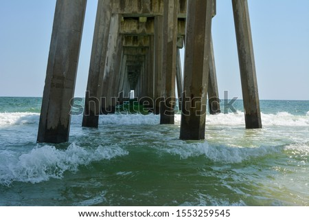 Pier pilings under Pensacola fishing pier on the tropical gulf coast of Florida