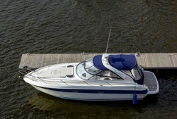 Pier speedboat. A marina lot. Yacht is moored at the quay. Marine parking of modern motor boats. Relaxation and fashionable vacation. Boats At The Marina. Top view.