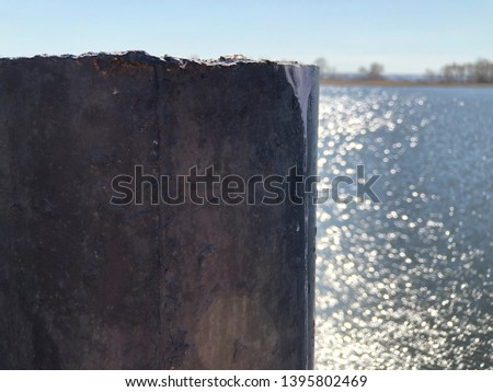 Pier support made of concrete pier poured into an iron pipe. Supports the pier over the water. Pier on the background of a river or sea. #1395802469