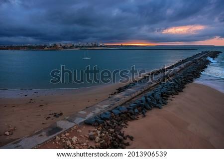 Pier to famous old farol de Portimao molhe este under gloomy sunset.Portugal Foto stock ©
