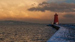 Pier to Poolbeg Lighthouse in Ireland Dublin bay,  Heavy snow and high winds after Storm