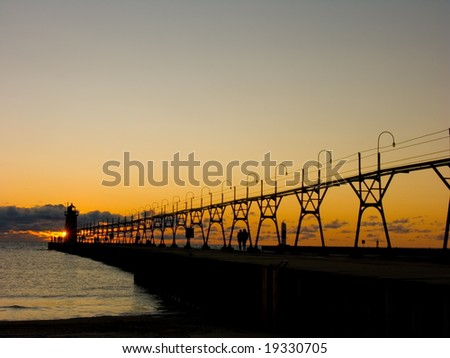 pier with catwalk and lighthouse at sunset