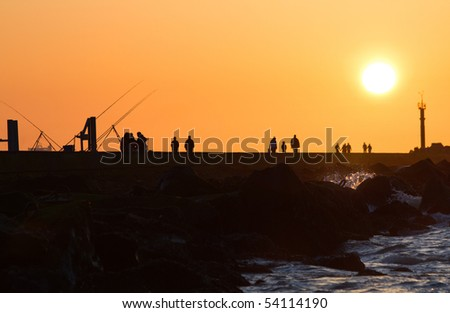 Pier with people fishing and walking - hazy and yellow sunset from volcano-dust in the air