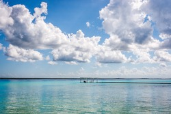 Pier with white clouds and blue lagoon water at the Laguna Bacalar, Chetumal, Quintana Roo, Mexico.