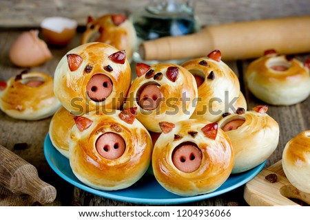 Pig buns stuffed with sausage - funny baking idea shaped cute piggy faces, symbolic food for new year 2019 #1204936066