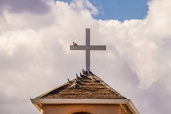 Pigeons roosting on a roof and on a cross against a dramatic cloudy sky