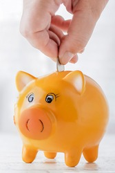 Piggy bank. A female hand puts coins into a piggy bank on the background of a window. Concept of savings, payment of a loan or investment. Copy space. vertical