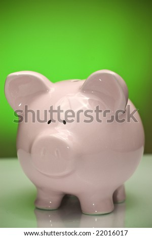 Piggy bank against green backdrop. Savings and economy concept.